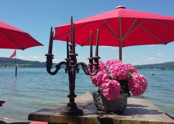 Tisch am See mit Blumen und Kerzenständer