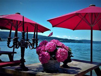 Sonnenschirme und Tisch mit Blumen vor dem See
